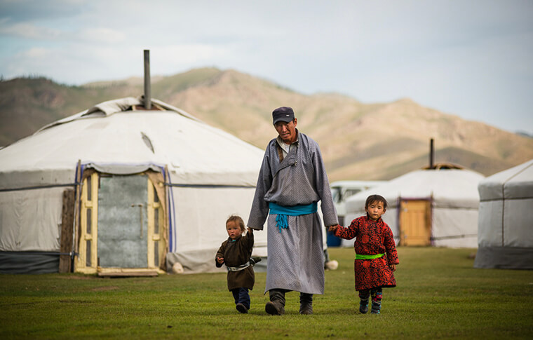 Mongolian local with two small children in hand walking through camp